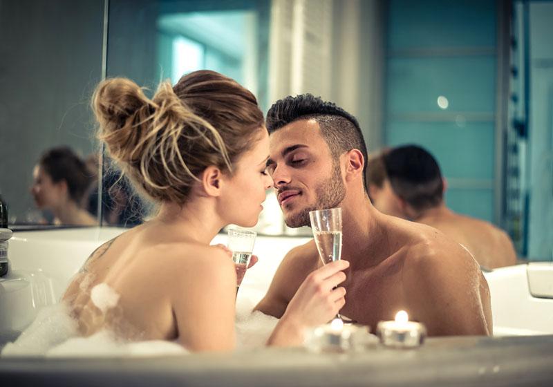 Joven pareja feliz disfrutando del baño en el jacuzzi - Pareja de amantes besándose en una piscina con jacuzzi