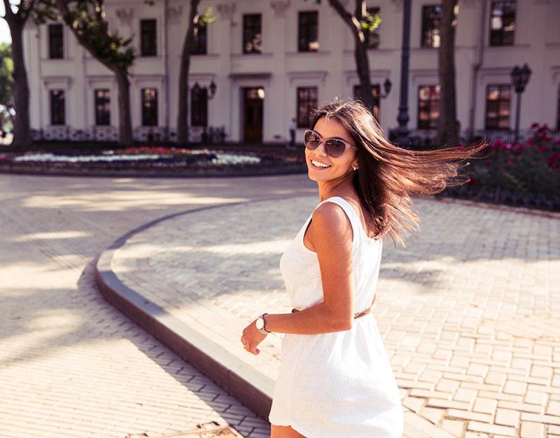Mujer feliz en gafas de sol y vestido caminando al aire libre. Mirando a la cámara