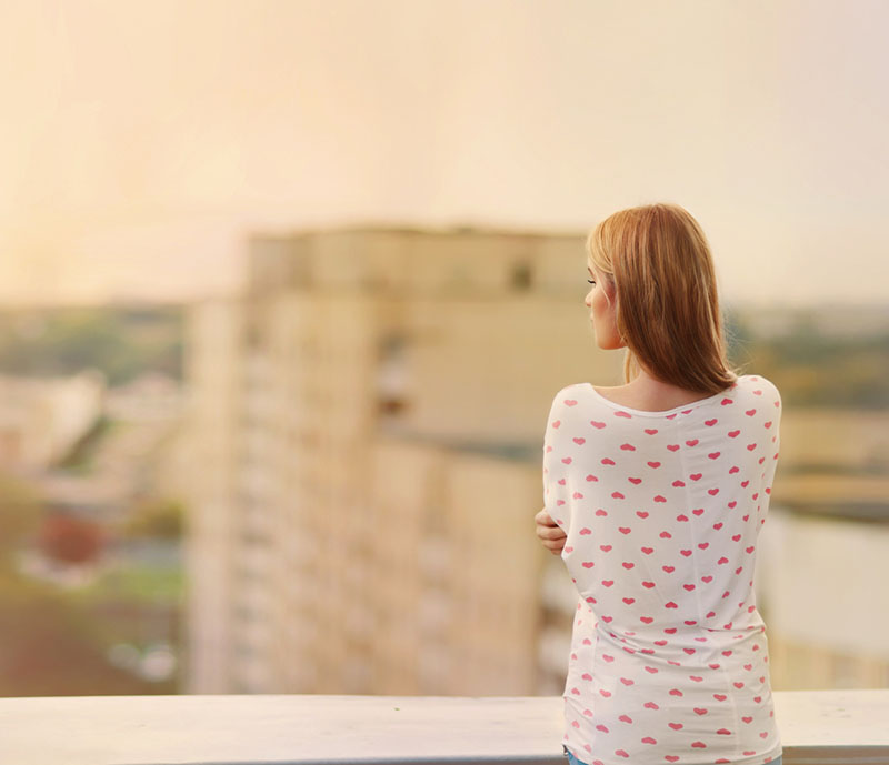 Hermosa rubia se para al borde del techo