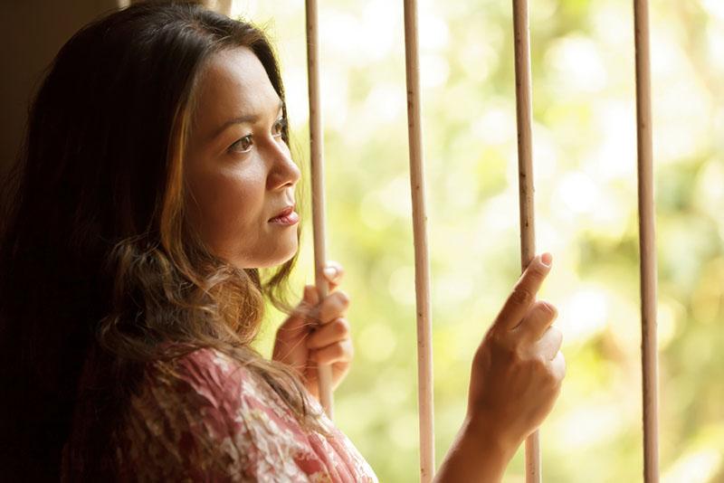 mujer triste nostálgica sosteniendo rejas y mirando afuera