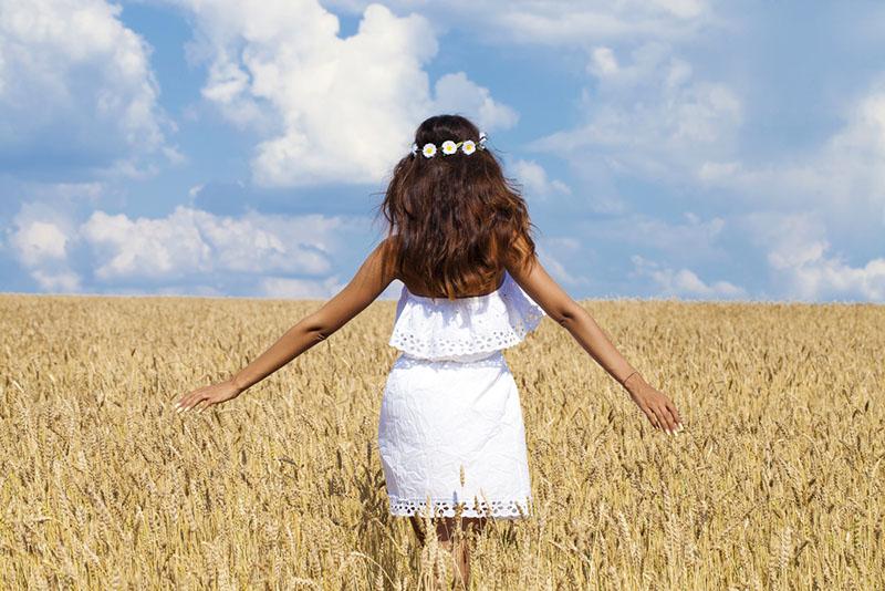 Hermosa mujer joven en vestido blanco en campo de trigo dorado
