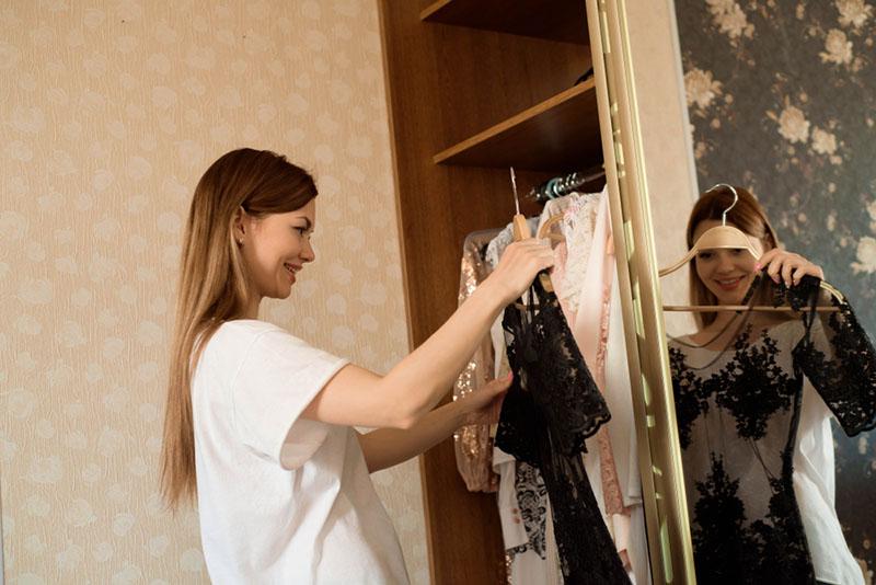 mujer eligiendo ropa delante del armario lleno